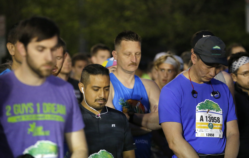 Photo - Runners stand for 168 seconds of silence before the Oklahoma City Marathon in Oklahoma City,  Sunday, April 29, 2018. Photo by Sarah Phipps, The Oklahoman