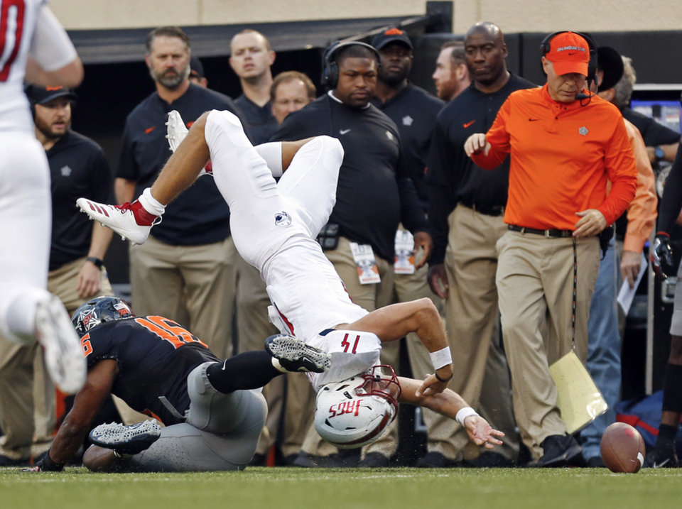 Photo - South Alabama's Evan Orth (14) fumbles after a tackle by Oklahoma State's Devin Harper (16) in the first quarter during a college football game between Oklahoma State (OSU) and South Alabama at Boone Pickens Stadium in Stillwater, Okla., Saturday, Sept. 8, 2018. Photo by Nate Billings, The Oklahoman