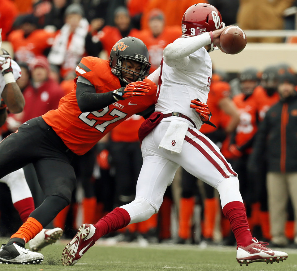 Photo - Oklahoma State's Lyndell Johnson (27) pressures Oklahoma's Trevor Knight (9) during the Bedlam college football game between the Oklahoma State University Cowboys (OSU) and the University of Oklahoma Sooners (OU) at Boone Pickens Stadium in Stillwater, Okla., Saturday, Dec. 7, 2013. Photo by Nate Billings, The Oklahoman