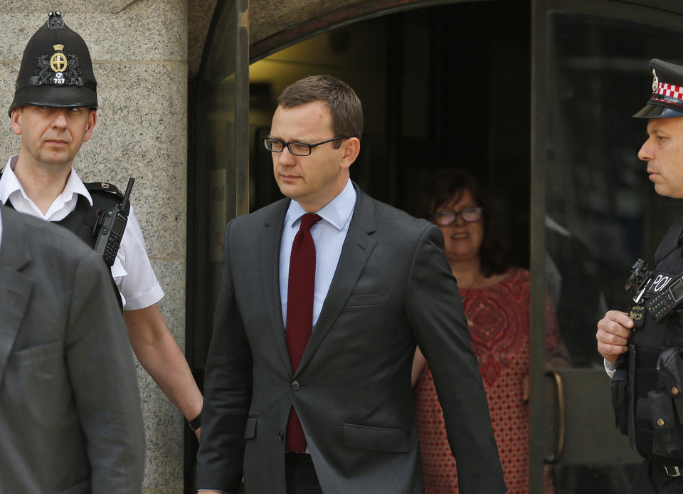 Photo - Andy Coulson, left, former News of the World editor and the former spin doctor of British Prime Minister David Cameron, leaves the Central Criminal Court in London, Wednesday, June 25, 2014. Coulson was convicted of phone hacking Tuesday, but fellow editor Rebekah Brooks was acquitted after a monthslong trial centering on illegal activity at the heart of Rupert Murdoch's newspaper empire. A judge on Wednesday dismissed the jury at Britain's phone-hacking trial after it failed to reach a verdict on two final counts, having convicted him of hacking a day earlier. Judge John Saunders ended the trial after jurors said they could not agree whether Coulson and ex-royal editor Clive Goodman were guilty of paying police officers for royal phone directories. Prosecutors said they would announce next week whether they would seek a retrial. (AP Photo/Lefteris Pitarakis)
