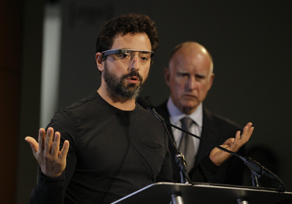 Photo -   Google co-founder Sergey Brin, left, wearing internet glasses, gestures while speaking as California Gov. Edmund G. Brown Jr., right, listens during a bill signing for driverless cars at Google headquarters in Mountain View, Calif., Tuesday, Sept. 25, 2012. The legislation will open the way for driverless cars in the state. Google, which has been developing autonomous car technology and lobbying for the legislation has a fleet of driverless cars that has logged more than 300,000 miles (482,780 kilometers) of self-driving on California roads. (AP Photo/Eric Risberg)