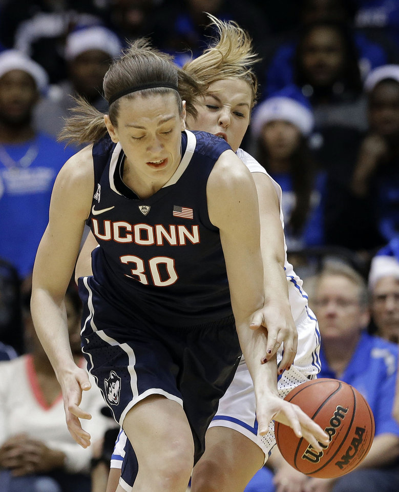 Photo - Connecticut's Breanna Stewart, left,  and Duke's Tricia Liston, right, reach for the ball during the first half of an NCAA college basketball game in Durham, N.C., Tuesday, Dec. 17, 2013. (AP Photo/Gerry Broome)