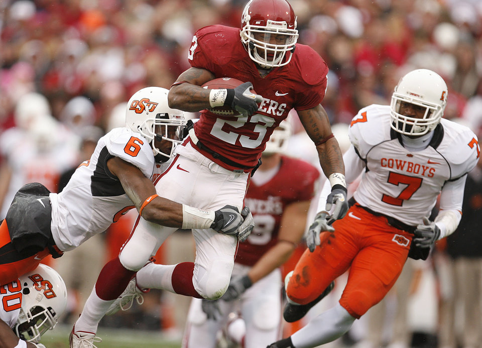 Photo - Oklahoma's Allen Patrick (23) takes the ball up field past Oklahoma State's Ricky Price (6) and Martel Van Zant (7) during the first half of the college football game between the University of Oklahoma Sooners (OU) and the Oklahoma State University Cowboys (OSU) at the Gaylord Family-Memorial Stadium on Saturday, Nov. 24, 2007, in Norman, Okla.  Photo By Bryan Terry, The Oklahoman