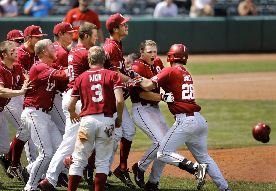 Photo - OU batter Sheldon Neuse, second from right, is mobbed by teammates after his hit in the ninth inning brought Craig Akin, #3, home for the Sooners' winning run. OU trailed most of the game but were able to score runs late in the game to defeat Texas Tech, 9-8, in the Big 12 Baseball Tournament on Thursday afternoon, May 22, 2014.   Photo by Jim Beckel, The Oklahoman