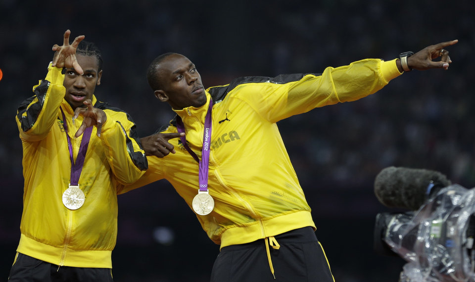 Photo -   Jamaica's Usain Bolt and Yohan Blake celebrate as they receive their gold medals for the men's 4x100-meter during the athletics in the Olympic Stadium at the 2012 Summer Olympics, London, Saturday, Aug. 11, 2012. (AP Photo/Matt Slocum)
