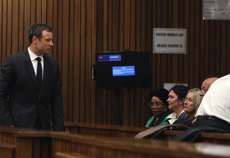 Photo - Oscar Pistorius, left, towards the parents of the late Reeva Steenkamp, June, second from right and Barry Steenkamp, right, on his arrival at court for his murder trial, in Pretoria, South Africa, Friday, Aug. 8, 2014. The chief defense lawyer for Oscar Pistorius delivered final arguments in the athlete's murder trial on Friday, alleging that Pistorius thought he was in danger when he killed girlfriend Reeva Steenkamp and also that police mishandled evidence at the house where the shooting happened. (AP Photo/ Themba Hadebe, Pool)