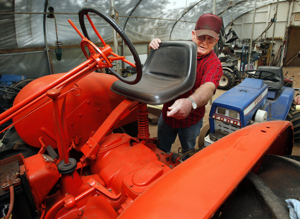 Photo - L.G. Wakefield and his tractor on Wednesday, May 2, 2012, in Tuttle, Okla.  This tractor overturned and landed on top of him earlier this year while he was trying to bring down a tree on his property.  Photo by Steve Sisney, The Oklahoman