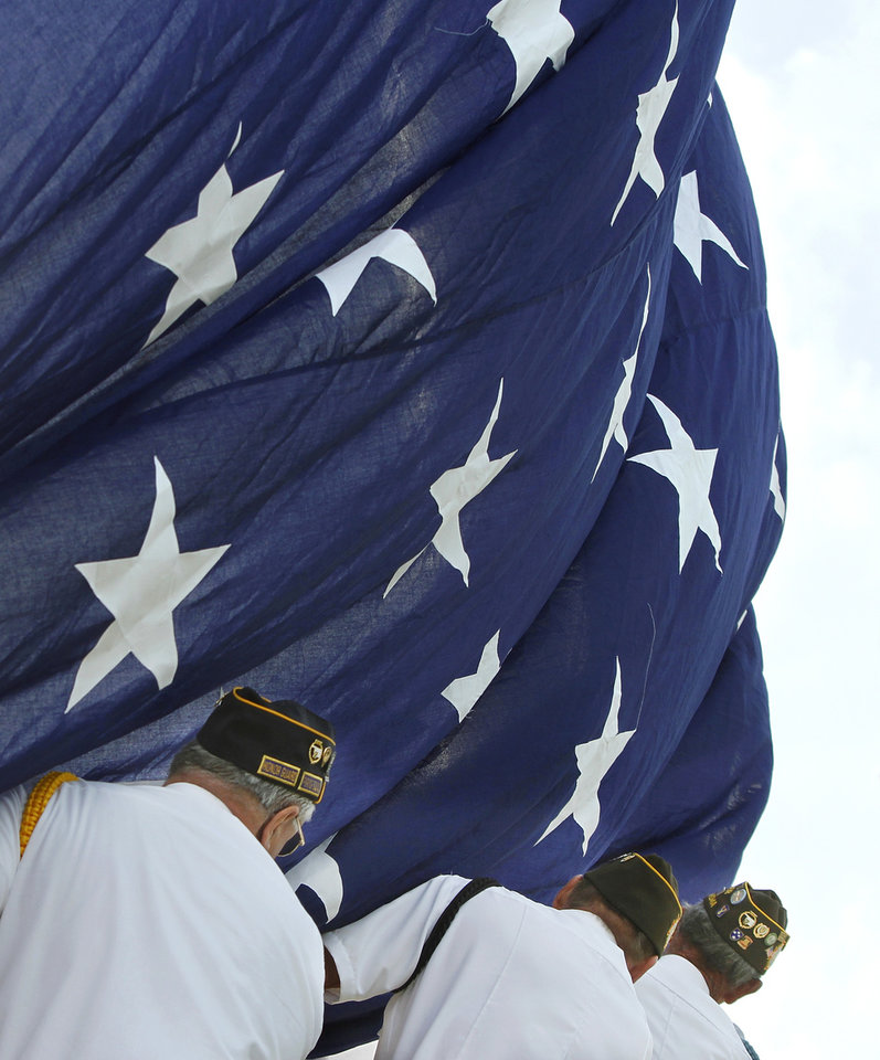 Three men hold tight to the large American flag as it is attached to the pole while being raised. They clutch the fabric so the wind won't blow it onto the ground before it is completely raised. Veterans from VFW Post 1118 in Cushing and members of the Honor Guard from American Legion Post 108 in Cushing helped raise the 30 x 50 foot American flag. Citizens of Drumright celebrated Flag Day by raising a  huge American flag 100 feet into the air above  Cleo Hutchison Centennial Memorial Park Thursday morning,   June 14,  2012.    Photo by Jim Beckel, The Oklahoman