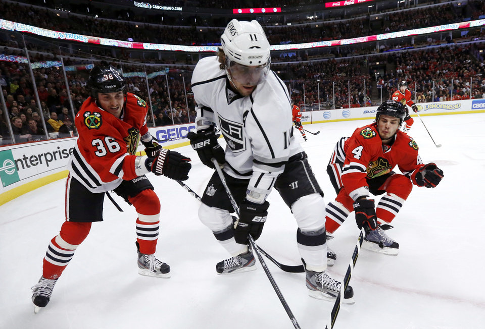 Photo - Chicago Blackhawks center Dave Bolland (36) and defenseman Niklas Hjalmarsson (4), of Sweden, put pressure on Los Angeles Kings center Anze Kopitar, of Slovenia, during the first period of an NHL hockey game, Monday, March 25, 2013, in Chicago. (AP Photo/Charles Rex Arbogast)