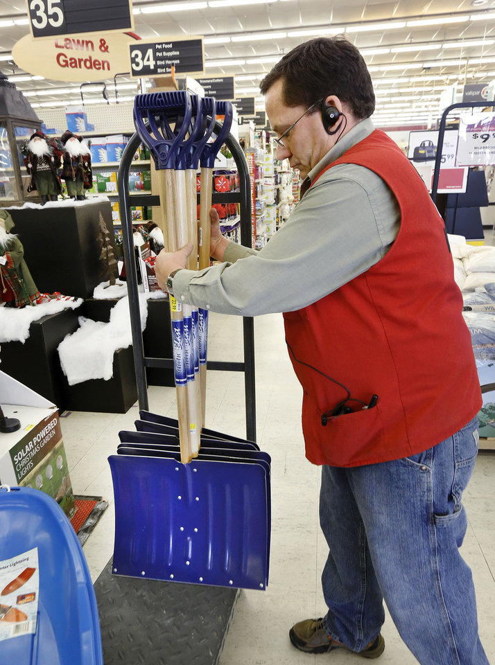 Photo - Jim Robinson adds more snow shovels to a winter tools display in the Westlake Ace Hardware store at SW 44 and Western on Wednesday afternoon, Dec. 4, 2013.  Robinson, a manager at the store, said a number of customers have purchased shovels and scrapers, but he reported even higher sales of tube sand and ice melt. Photo by Jim Beckel, The Oklahoman