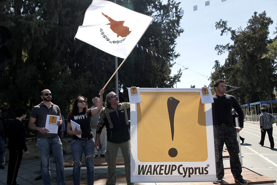 """Photo - Protesters chant slogans after the end of a parade for Greek Independence Day celebrations in capital Nicosia, Cyprus, Monday, March 25, 2013. Cyprus secured what its politicians described as a """"painful"""" solution to avert imminent bankruptcy, agreeing early Monday to slash its oversize banking sector and make large account holders take losses to help pay to secure a last-minute euro10 billion (US$13 billion) bailout. (AP Photo/Petros Giannakouris)"""