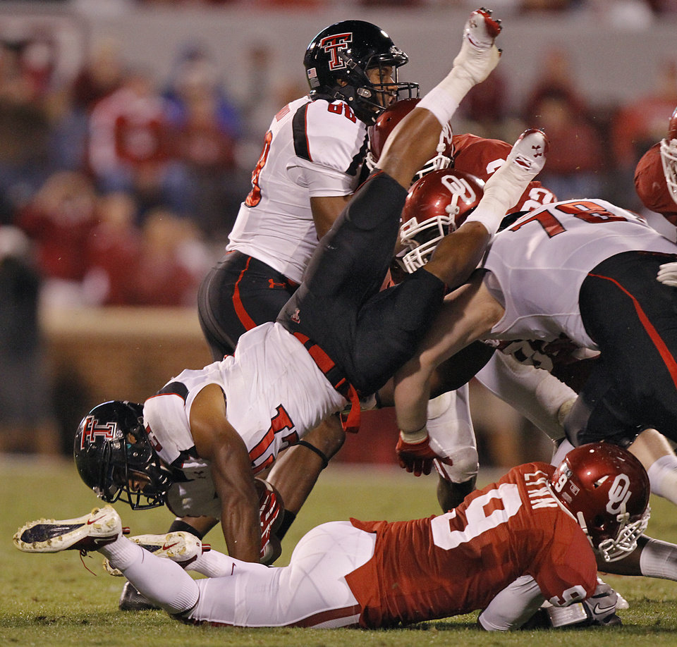 Photo - Texas Tech's DeAndre Washington (21) is upended by Oklahoma's Gabe Lynn (9) during the college football game between the University of Oklahoma Sooners (OU) and Texas Tech University Red Raiders (TTU) at the Gaylord Family-Oklahoma Memorial Stadium on Saturday, Oct. 22, 2011. in Norman, Okla. Photo by Chris Landsberger, The Oklahoman