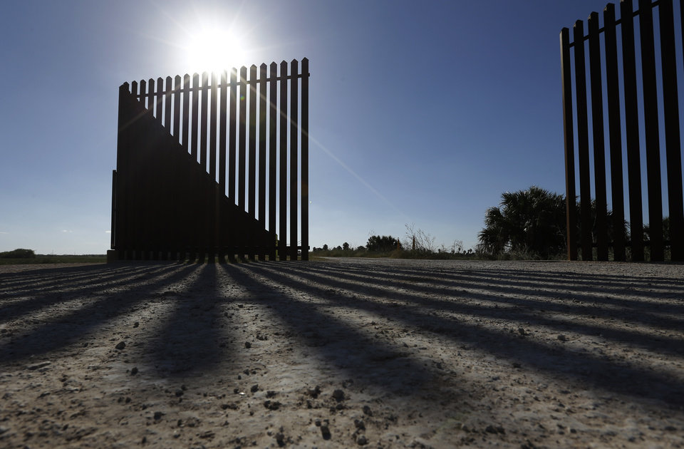In this Sept. 4, 2012, photo, the sun casts a shadow on the U.S.-Mexico border fence that passes through the Nature Conservancy\'s southernmost preserve in Brownsville, Texas. Since 2008, hundreds of landowners on the border have sought fair prices for property that was condemned to make way for the fence, but many of them received initial offers that were far below market value. (AP Photo/Eric Gay)