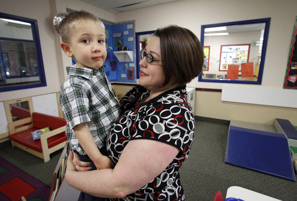 Photo -   In this April 4, 2012, photo, Kelly Andrus holds her son Bradley in his classroom at Children's Choice Learning Centers Inc., in Lewisville, Texas. Bradley, who turns three in a couple of weeks, was diagnosed a year ago with mild autism. For the first time in nearly two decades, experts want to rewrite the definition of autism. Some parents fear that if it's narrowed and their kids lose the label, they may also lose out on special therapist. (AP Photo/Tony Gutierrez)