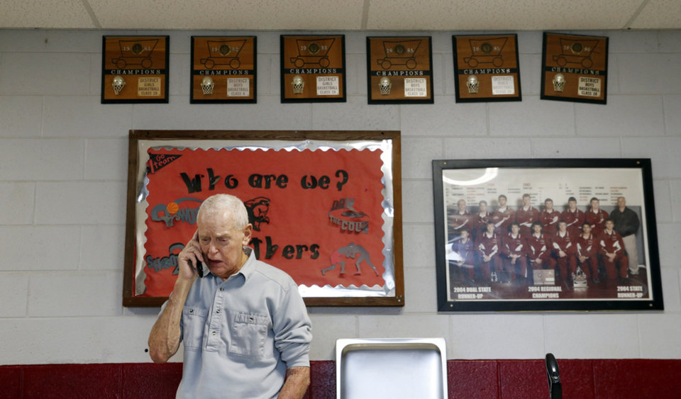 Photo - Coach Joe Gilbert takes a phone call from another coach while inside the fieldhouse named after him at Barnsdall High School in Barnsdall, Okla., Tuesday, Feb. 18, 2020. Gilbert, currently the girls basketball coach, has coached at Barnsdall since 1954. [Nate Billings/The Oklahoman]