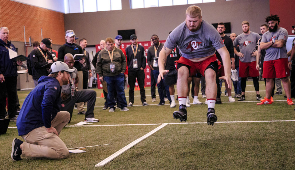 Photo - Ben Powers records his broad jump as he works out for NFL scouts during the University of Oklahoma football pro day at the University of Oklahoma in Norman, Okla. on Wednesday, March 13, 2019.   Photo by Chris Landsberger, The Oklahoman