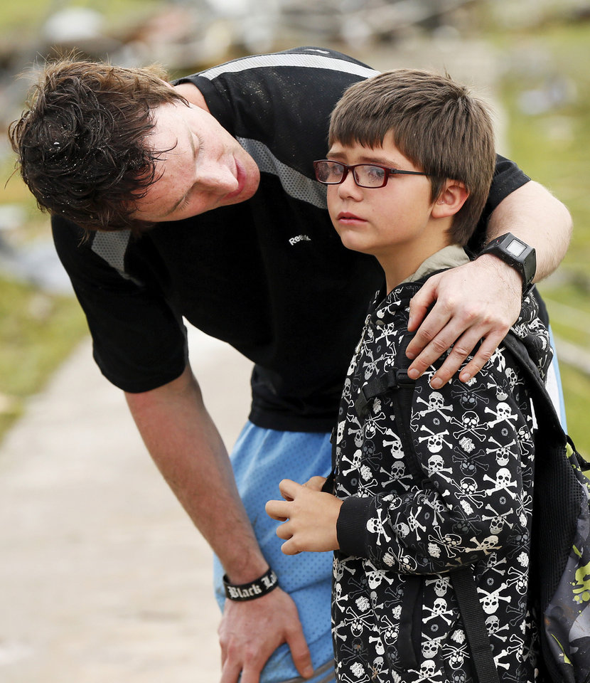 TORNADO DAMAGE / TORNADO AFTERMATH: Briarwood Elementary P.E. teacher Mike Murphy comforts Aiden Stuck, 7, as he waits for his mother at the school after a tornado destroyed Briarwood Elementary and struck south Oklahoma City and Moore, Okla., Monday, May 20, 2013. Photo by Nate Billings, The Oklahoman