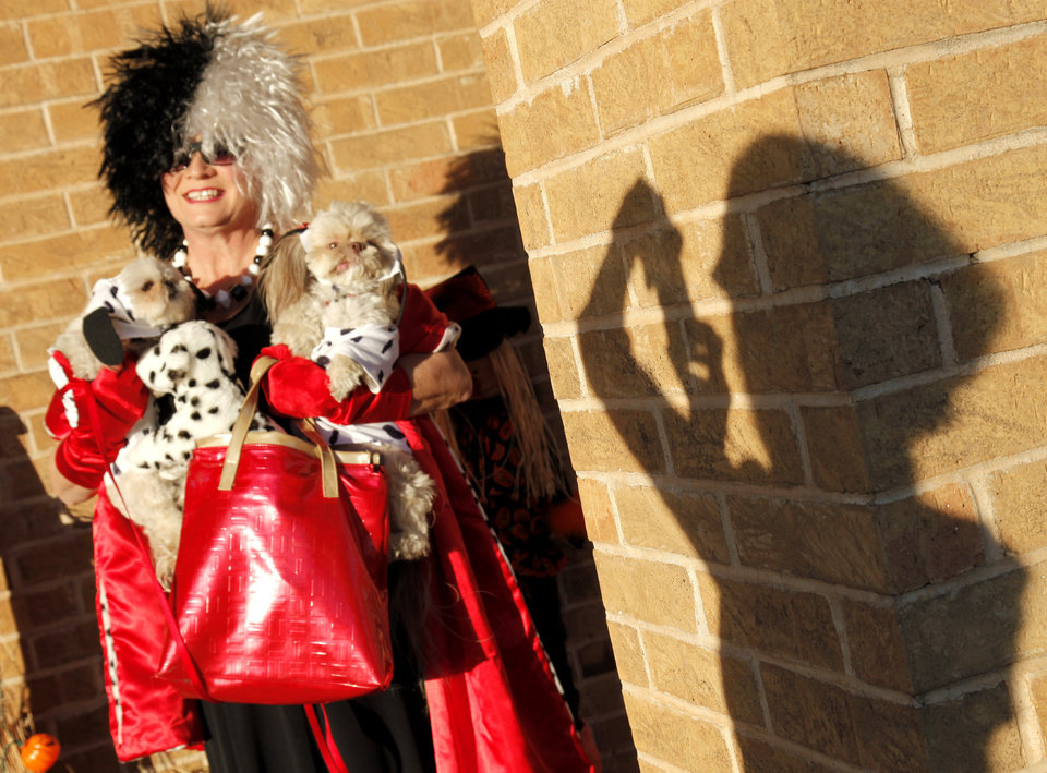 Janice Bingaman (shown in shadow) takes a photo of Nelda Kirk is dressed as Cruella de Ville with her Imperial Shih-Tzus, Molly and Charlie, dressed as dalmatians, during the Howl-O-Weenie costume party for pets at Cherokee Hills Veterinary Hospital Wednesday, Oct. 27, 2010. Photo by Doug Hoke, The Oklahoman