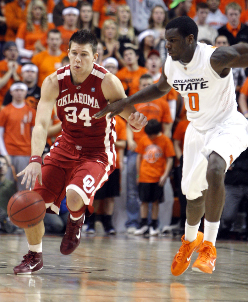 Photo - Oklahoma's Cade Davis (34) tries to get past Oklahoma State's Jean-Paul Olukemi (0) during the Bedlam men's college basketball game between the University of Oklahoma Sooners and Oklahoma State University Cowboys at Gallagher-Iba Arena in Stillwater, Okla., Saturday, February, 5, 2011. Photo by Sarah Phipps, The Oklahoman
