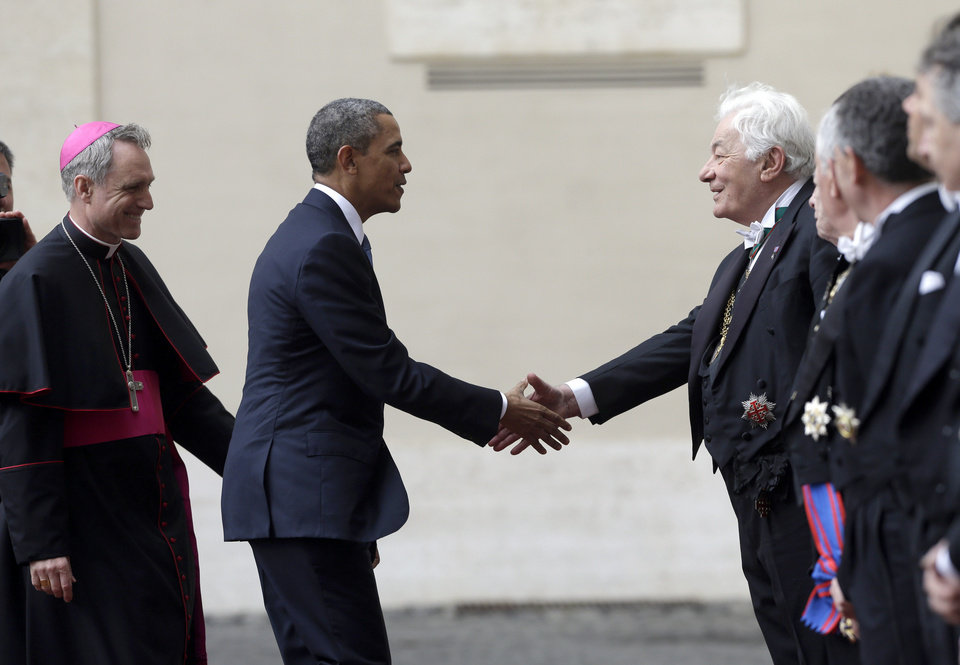 Photo - President Barack Obama, followed by Archbishop George Gaenswein, prefect of the papal household, is welcomed by Papal gentlemen as he arrives at the Vatican to meet Pope Francis, Thursday, March 27, 2014. Obama is the ninth president to make an official visit to the Vatican. His audience marks a change of pace for the president, who has devoted the past three days of a weeklong, four-country trip to securing European unity against Russia's aggressive posture toward Ukraine. (AP Photo/Alessandra Tarantino)