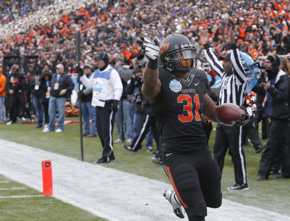 Photo - Oklahoma State's Jeremy Smith (31) celebrates a touchdown during the Heart of Dallas Bowl football game between the Oklahoma State University (OSU) and Purdue University at the Cotton Bowl in Dallas,  Tuesday,Jan. 1, 2013. Photo by Sarah Phipps, The Oklahoman