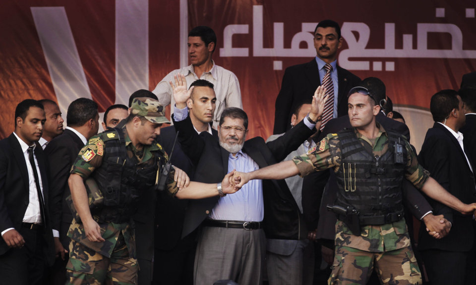 Photo -   FILE - In this Friday, June 29, 2012 file photo, Egypt's new President-elect Mohammed Morsi waves to supporters after giving a speech at Tahrir Square in Cairo, Egypt. Standing before tens of thousands of adoring supporters in Tahrir Square, Morsi opened his jacket to show he is not wearing a bullet-proof vest. The message is clear: He has nothing to fear because he sees himself as the legitimate representative of Egypt's uprising. His speeches reveal a populist bent, making generous promises that many are skeptical he can keep. And though he began as an awkward and uninspiring speaker, he appears to be striving to reinvent his decidedly uncharismatic public persona. (AP Photo/Khalil Hamra, File)