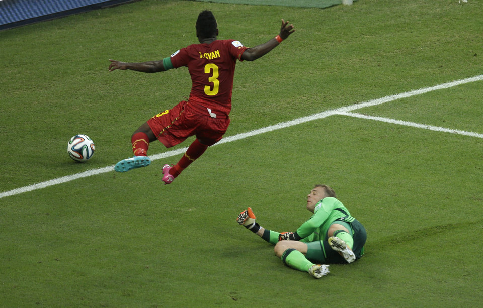 Photo - Ghana's Asamoah Gyan, left, leaps as he runs past Germany's goalkeeper Manuel Neuer during the group G World Cup soccer match between Germany and Ghana at the Arena Castelao in Fortaleza, Brazil, Saturday, June 21, 2014. (AP Photo/Themba Hadebe)