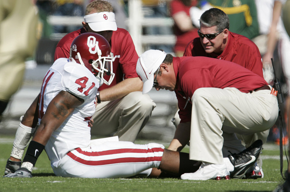 Photo - Oklahoma trainers tend to the knee of Darien Williams (41) in the first half during the University of Oklahoma Sooners (OU) college football game against Baylor University Bears (BU) at Floyd Casey Stadium, on Saturday, Nov. 18, 2006, in Waco, Texas.     by Chris Landsberger, The Oklahoman