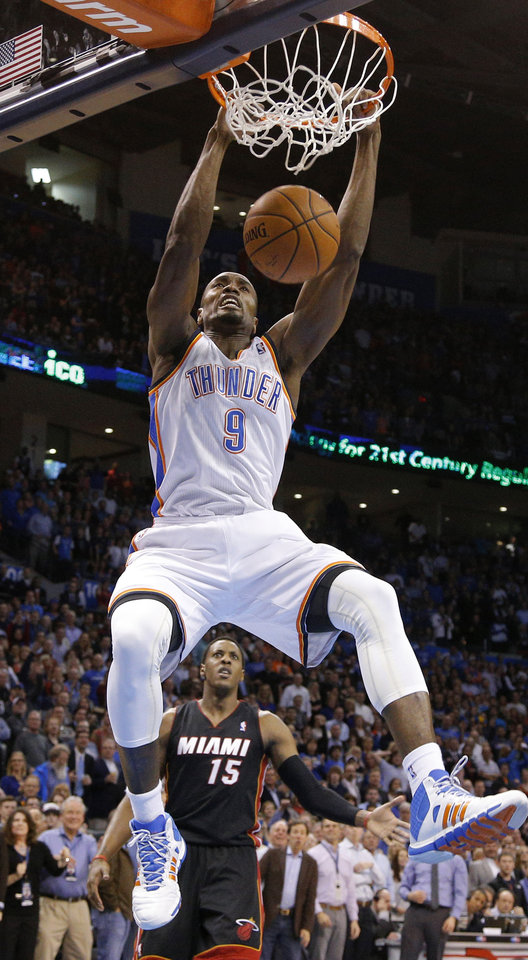 Photo - Oklahoma City's Serge Ibaka (9) dunks the ball as Miami's Mario Chalmers (15) watches during an NBA basketball game between the Oklahoma City Thunder and the Miami Heat at Chesapeake Energy Arena in Oklahoma City, Thursday, Feb. 20, 2014. Photo by Bryan Terry, The Oklahoman