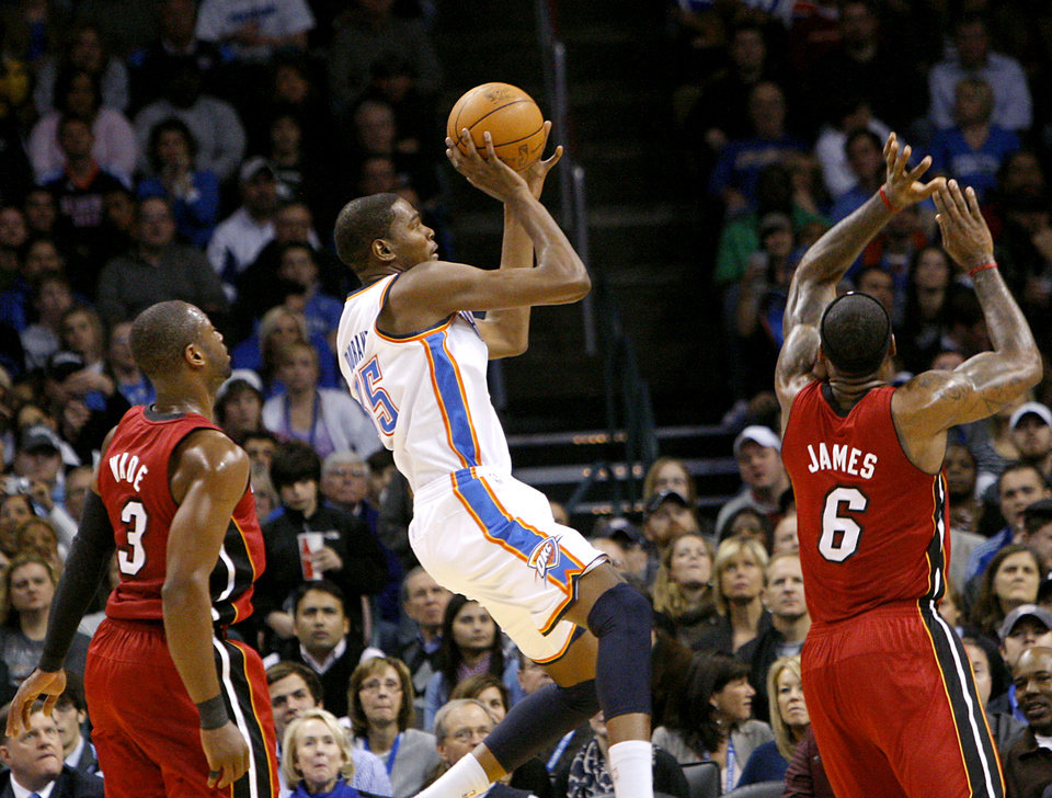 Photo - Oklahoma City's Kevin Durant puts up a shot that was blocked by Miami's LeBron James (right) during their NBA basketball game at the OKC Arena in Oklahoma City on Thursday, Jan. 30, 2011. Photo by John Clanton, The Oklahoman