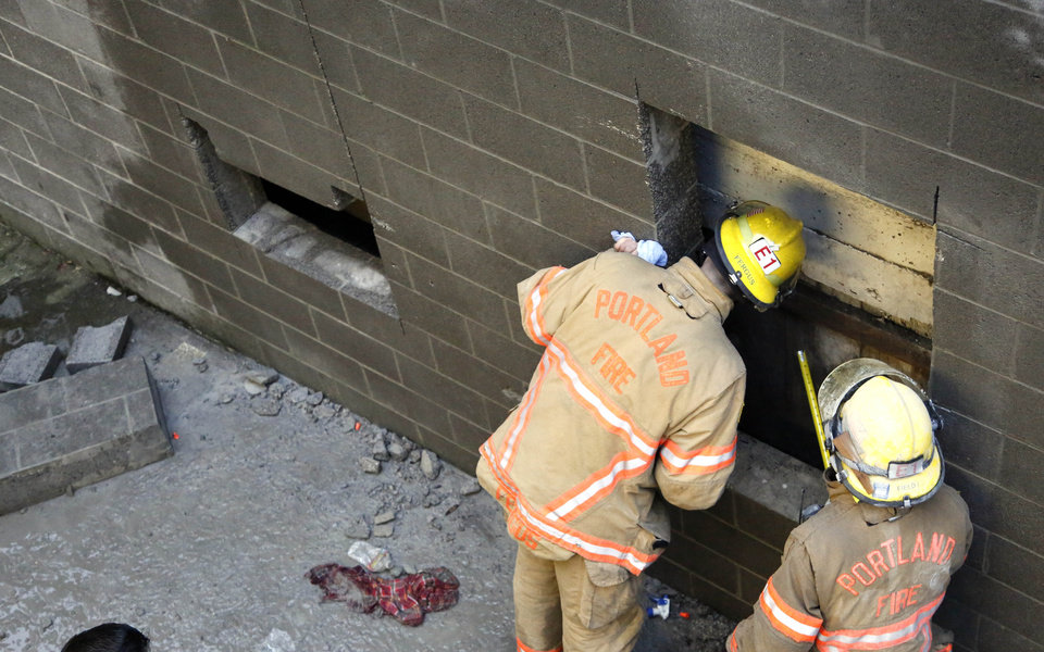 Photo - Portland firefighters Fred Williams, right, and Gary Fergus check one of two holes that were cut out to free a woman who fell part of the way down the 20-foot wall and got herself stuck between two buildings in Portland, Ore., Wednesday, Jan. 16, 2013.  The woman spent about four hours in a space less than a foot wide Wednesday morning. In addition to the an air bag, rescuers also cut a hole and used a soapy substance to lubricate the concrete block walls to remove the woman.(AP Photo/Don Ryan)