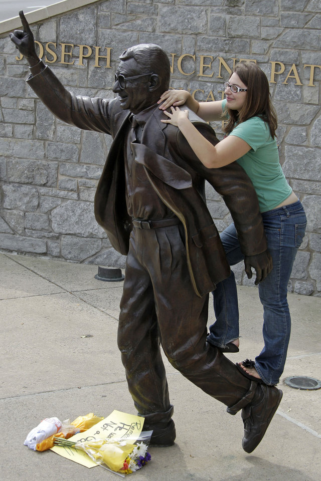 Photo -   Megan Toth of State College, Pa., climbs on a statue of former Penn State University head football coach Joe Paterno outside Beaver Stadium in State College, Pa., Friday, July 13, 2012. (AP Photo/Gene J. Puskar)