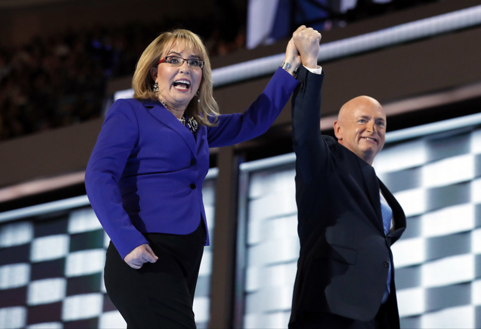 Photo - Former Rep. Gabby Giffords, D-Ariz, and her husband Astronaut Mark Kelly (ret.), walk off the stage after speaking during the third day session of the Democratic National Convention in Philadelphia, Wednesday, July 27, 2016. (AP Photo/Carolyn Kaster)