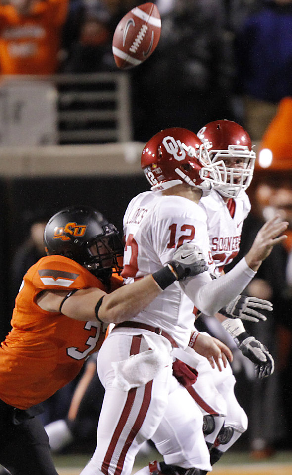 Photo - Oklahoma State's Alex Elkins (37) hits Oklahoma's Landry Jones (12) to cause a fumble during the Bedlam college football game between the Oklahoma State University Cowboys (OSU) and the University of Oklahoma Sooners (OU) at Boone Pickens Stadium in Stillwater, Okla., Saturday, Dec. 3, 2011. Photo by Chris Landsberger, The Oklahoman