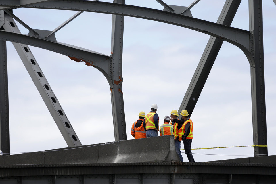 Photo - Workers look up at a damaged beam on a section of bridge adjacent to a collapsed portion of the Interstate 5 bridge at the Skagit River Friday, May 24, 2013, in Mount Vernon, Wash. A truck carrying an oversize load struck the four-lane bridge on the major thoroughfare between Seattle and Canada, sending a section of the span and two vehicles into the Skagit River below Thursday evening. All three occupants suffered only minor injuries.  (AP Photo/Elaine Thompson)
