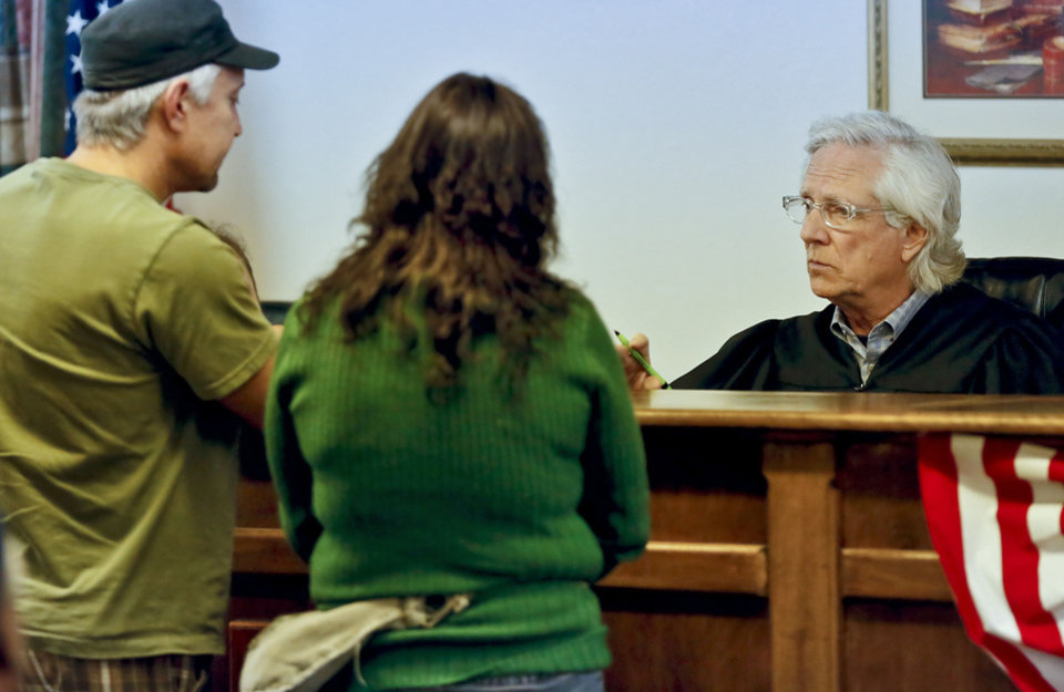 Photo - Municipal Judge Stephen Haynes speaks to two individuals appearing in a night court session in Valley Brook on Wednesday.  CHRIS LANDSBERGER - The Oklahoman