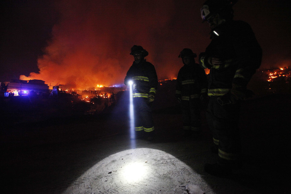 Photo - A firefighter shines a flashlight as he stands with others near burning homes as a forest fire rages towards urban areas in the city of Valparaiso, Chile, Sunday April 13, 2014. Authorities say the first fire has destroyed at least 150 homes and is forcing evacuations.( AP Photo/ Luis Hidalgo)