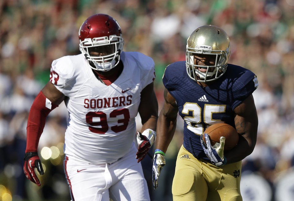 Notre Dame's Tarean Folston (25) runs past Oklahoma's Jordan Wade (93) during the first half of an NCAA college football game on Saturday, Sept. 28, 2013, in South Bend, Ind. (AP Photo/Darron Cummings)  ORG XMIT: INDC107