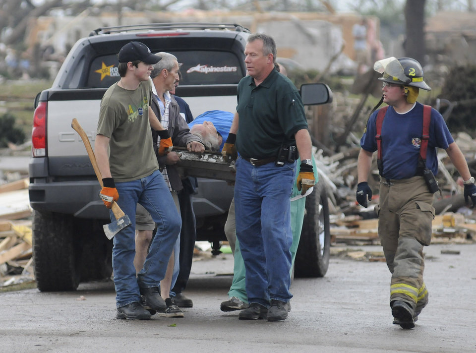 Photo - An injured person is removed from the Masters Drive area of Concord, Ala., after what appeared to be a tornado ripped through parts of the town late Wednesday, April 27, 2011. The damage in the area is extensive with homes and businesses destroyed and people injured.   (AP Photo/Birmingham News, Jeff Roberts)