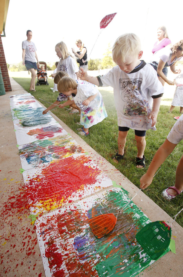 Photo - Left: Tyler Frankenfield, 3, slaps some paint as children paint with flyswatters Monday at the Edmond Multipurpose Activity Center.