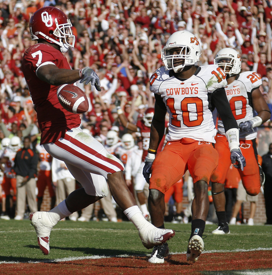 Photo - OU's DeMaro Murray scores a touchdown in front of OSU's Markelle Martin and Andre Sexton during the second half of the Bedlam college football game between the University of Oklahoma Sooners (OU) and the Oklahoma State University Cowboys (OSU) at the Gaylord Family-Oklahoma Memorial Stadium on Saturday, Nov. 28, 2009, in Norman, Okla.