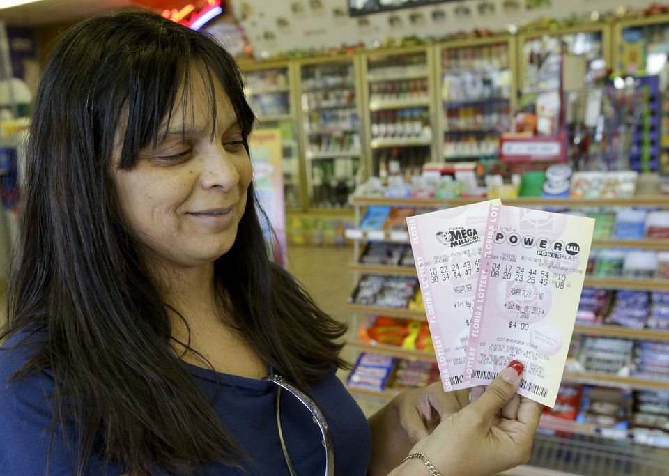 Photo - Lilly Sanchez holds up lotto tickets she purchased including a Powerball ticket seeking a payout of around $475 million,  Thursday, May 16, 2013, in Orlando, Fla.  The prize is the third largest in lottery history, and the winning numbers will be drawn on Saturday.(AP Photo/John Raoux)