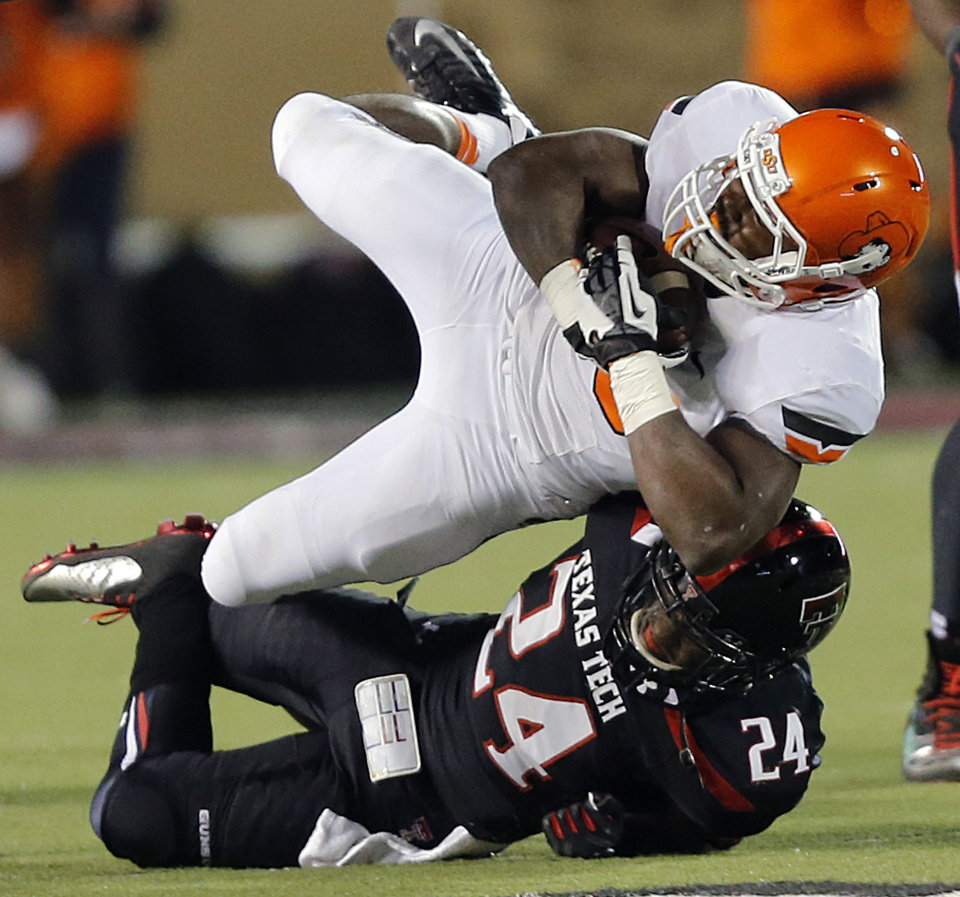 Texas Tech's Bruce Jones (24) brings down Oklahoma State 's Rennie Childs (23) during the college football game between the Oklahoma State University Cowboys (OSU) and the Texas Tech University Red Raiders (TTU) at Jones AT&T Stadium in Lubbock, Tex. on Saturday, Nov. 2, 2013.  Photo by Chris Landsberger, The Oklahoman
