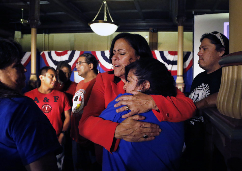 Photo - Democratic state Sen. Angela Giron hugs a crying supporter after giving her concession speech after she lost in a recall vote in Pueblo, Colo., Tuesday Sept. 10, 2013. Two Colorado state lawmakers who backed gun-control measures in the aftermath of the mass shootings in Colorado and Connecticut last year have been ousted in recall elections. (AP Photo/Brennan Linsley)