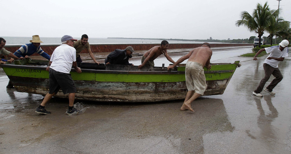 Photo -   People remove a boat from the water ahead of the arrival of Hurricane Sandy in Manzanillo, Cuba, Wednesday, Oct. 24, 2012. Hurricane Sandy pounded Jamaica with heavy rain as it headed for landfall near the country's most populous city on a track that would carry it across the Caribbean island to Cuba, and a possible threat to Florida. (AP Photo/Franklin Reyes)