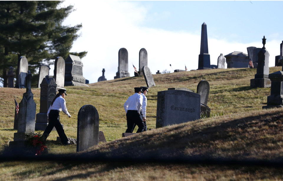 Photo - People walk at St. Rose of Lima parish cemetery before funeral services for Daniel Gerard Barden, one of the students killed during the Sandy Hook Elementary shooting, Wednesday, Dec. 19, 2012, in Newtown, Conn. Barden, 7, was killed when the gunman, Adam Lanza, walked into the school, Dec. 14, and opened fire, killing 26 people, including 20 children, before killing himself. (AP Photo/Julio Cortez)