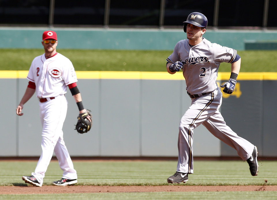 Photo - Milwaukee Brewers' Scooter Gennett, right, rounds the bases after hitting a solo home run off Cincinnati Reds starting pitcher Alfredo Simon during the first inning of a baseball game, Sunday, May 4, 2014, in Cincinnati. Reds shortstop Zack Cozart watches at left. (AP Photo/David Kohl)