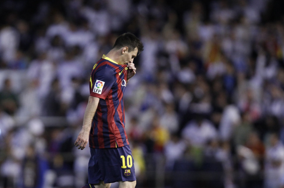 Photo - Barcelona's Lionel Messi touches his shirt  during the final of the Copa del Rey between FC Barcelona and Real Madrid at the Mestalla stadium in Valencia, Spain, Wednesday, April 16, 2014. (AP Photo/Alberto Saiz)