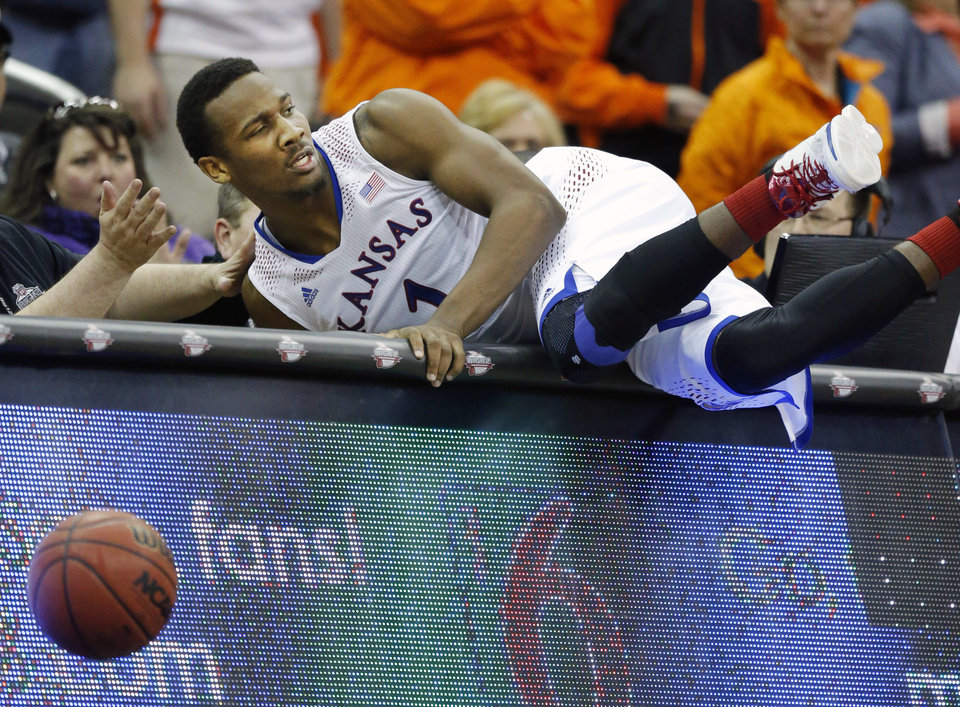 Photo - Kansas guard Wayne Selden, Jr. crashes into the scorers' table while chasing a loose ball during overtime of an NCAA college basketball game against Oklahoma State in the quarterfinals of the Big 12 Conference men's tournament in Kansas City, Mo., Thursday, March 13, 2014. Kansas defeated Oklahoma State 77-70 in overtime. (AP Photo/Orlin Wagner)