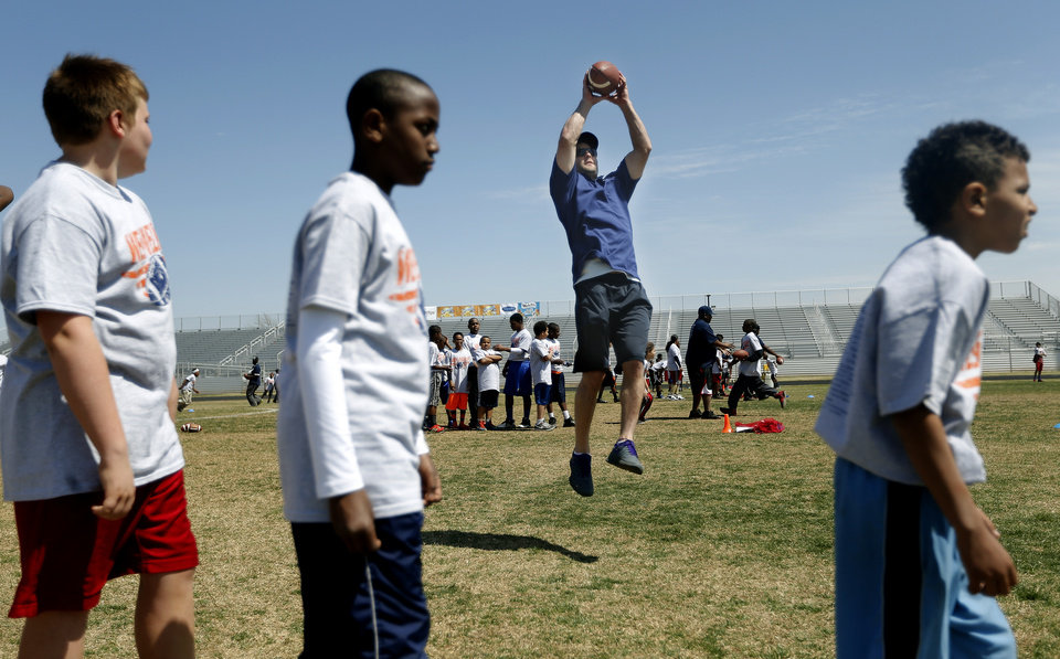Photo - Denver Broncos' Wes Welker catches a ball while leading receiving drills during the Wes Welker pro camp at Douglass High School in  Oklahoma City., Saturday, April 05, 2014. Photo by Sarah Phipps, The Oklahoman